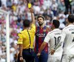 El árbitro Gil Manzano (i) saca la tarjeta amarilla al defensa del FC Barcelona Gerard Piqué (c) ante los jugadores del Real Madrid, James Rodríguez (2d) y Cristiano Ronaldo durante un partido de Liga de Primera División en el estadio Santiago Bernabéu. EFE/Archivo