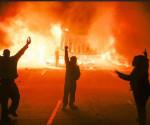 Manifestantes protestan ante un edificio en llamas durante los disturbios en Ferguson, Misuri, Estados Unidos, después de que el fiscal anunciara que un gran jurado había decidido no imputar al policía Darren Wilson por la muerte del joven Michael Brown. EFE