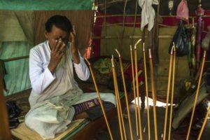 """La hechicera Lork Ta (que podría traducirse como """"ermitaña con poderes mágicos"""") reza en pali un conjuro que pasará al perfume que sostiene con las manos, y al ser rociado sobre una persona, podrá provocar el enamoramiento, en el monte Blanco, en la provincia de Kampot, al sur de Camboya. EFE"""