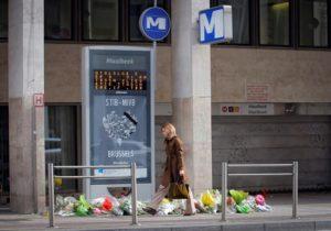 Una mujer camina junto a la entrada de la estación de metro de Maalbeek, decorada con ramos de flores, en Bruselas. EFE/Archivo